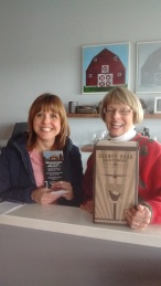 Jane Anderson receiving donation from Vicki Samaras at County Road Beer Company